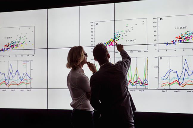Two people stood in front of large illuminated screen full of graphs and statistics.