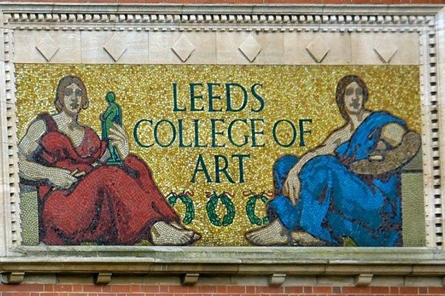 A photograph of the Leeds College of Art mosaic. Mosaic against a brick wall. Central panel reads 'Leeds College of Art' flanked by allegorical figures: Sculpture on the left, Painting on the right.