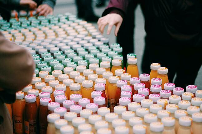 Photograph of an assortment of juice bottles taken from a high angle so you can just see the tops with different coloured labels.