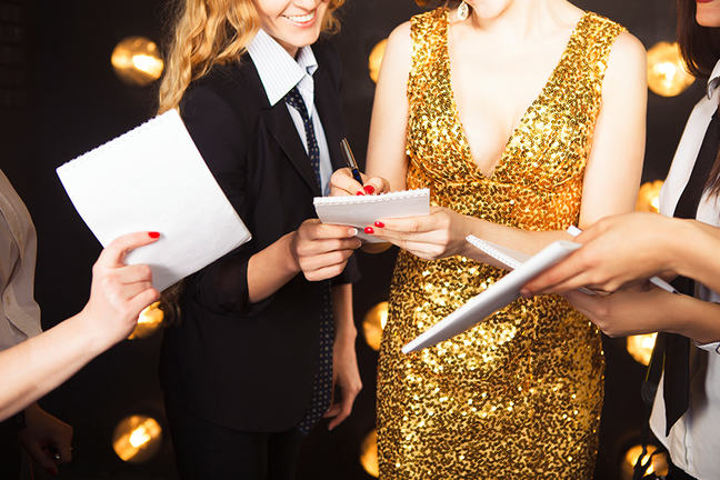 Female celebrity in gold sparkly dress signing autographs.