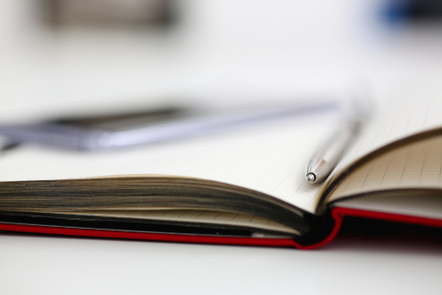 A book is open. A pen lies between the pages.