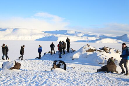 Decorative image, people wearing cold weather gear looking around a vast, hilly snow covered landscape.