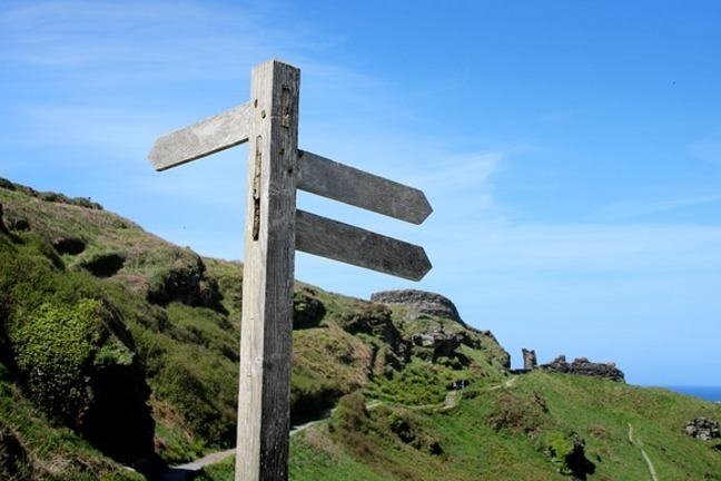 Photograph of a wooden signpost on the top of a hill in the countryside.  The signs and blank and point in several directions