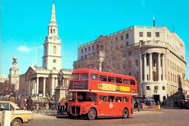 A double decker red bus drives through Trafalgar Square.