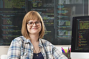 Woman smiling in front of screens showing lines of code
