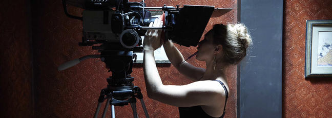 Filmmaking: a female cinematographer changing the lens on the camera