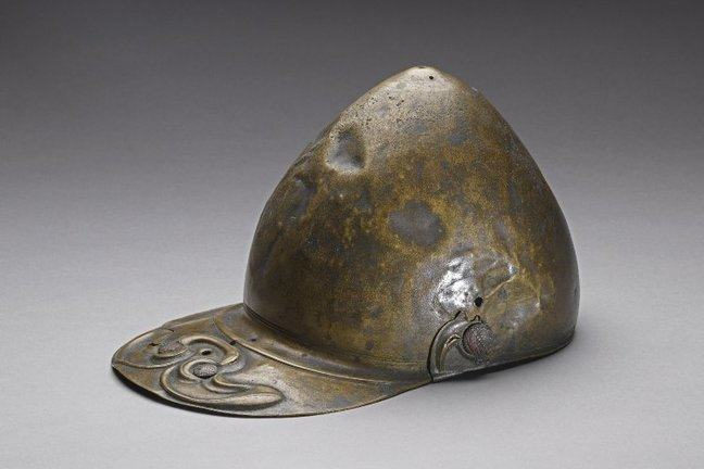 A peaked helmet from the Iron age, fabricateed from beaten copper, it has a slightly pointed crown and a metal peak.