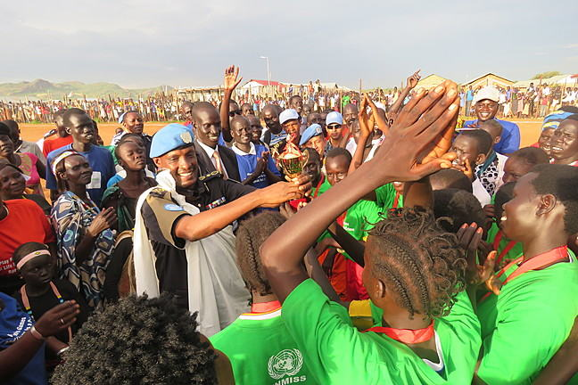 group of female football players, and soldiers group around a trophy in South Sudan