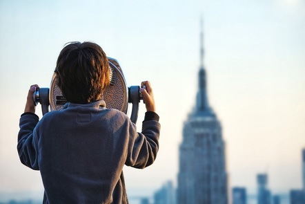 Boy looks at Empire State building through a tower viewer.