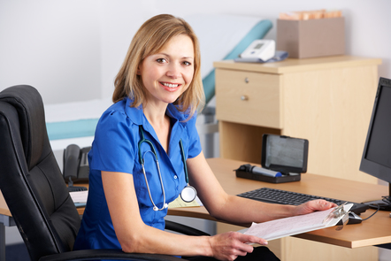 Female GP sitting at her desk with a clipboard (©Shutterstock)