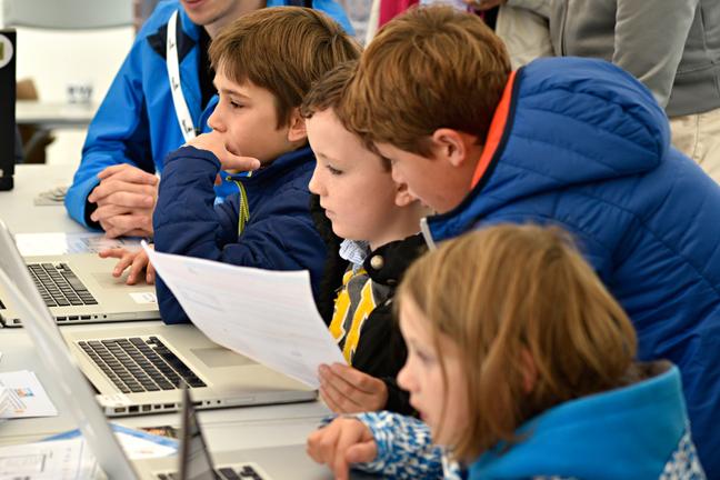 Children learning at laptops