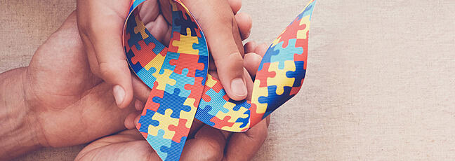 hand with a jigsaw patterned ribbon