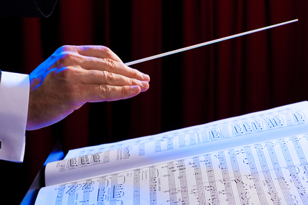 A conductor's hand moving over a musical score