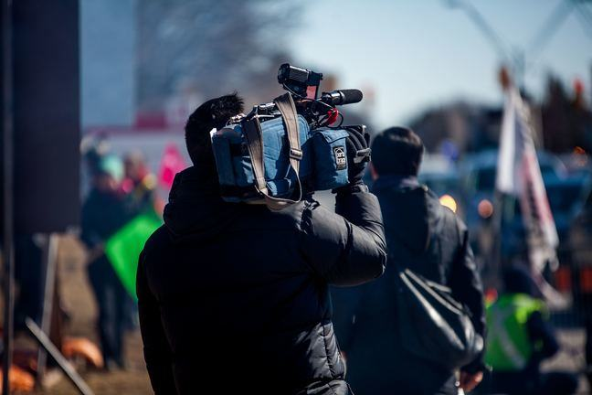 A camera crew shoulder their equipment through the street