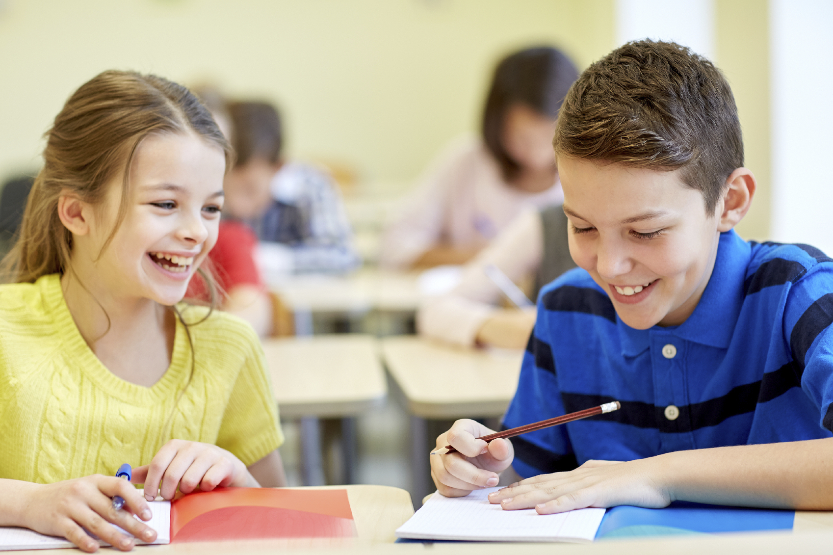 Girl and boy in classroom writing a story in exercise books and smiling