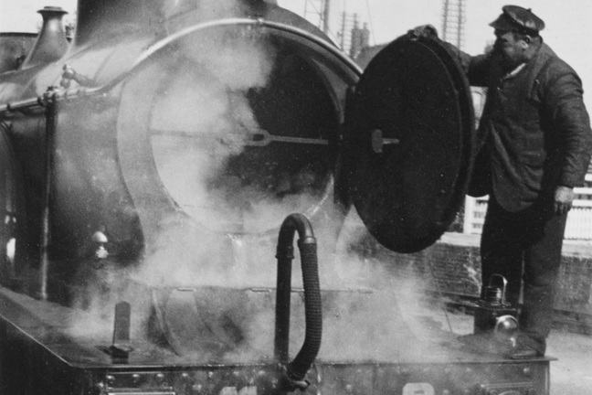 Black and white image of a driver inspecting the smokebox of a locomotive