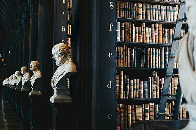 A procession of marble busts stretching back into the distance inside a library with old books visible on black shelves.