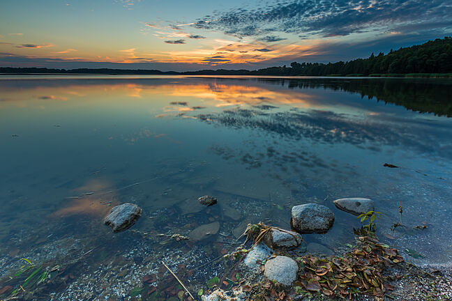 Beautiful lake at sunset landscape with cloudy sky reflecting in water.