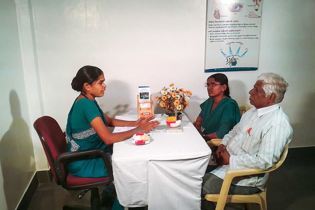 Health worker talking with patient and family