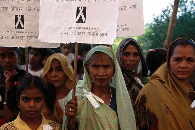 Large group of Indian women protesting with signs