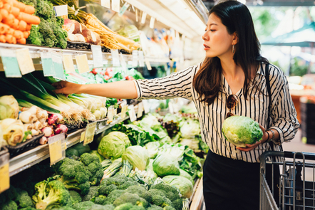 Woman selects lettuce and leeks from vegetable section in supermarket.
