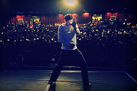 male performer on stage, his back to the audience