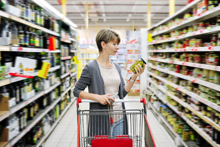 Shopper in a supermarket looking at a food label.