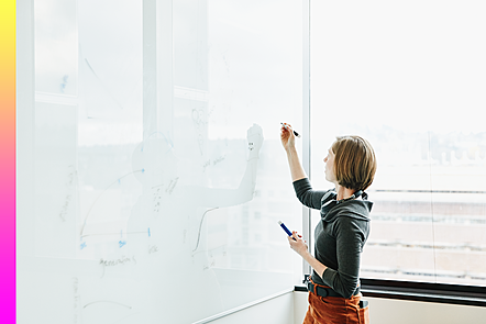 Female working on a whiteboard in an office