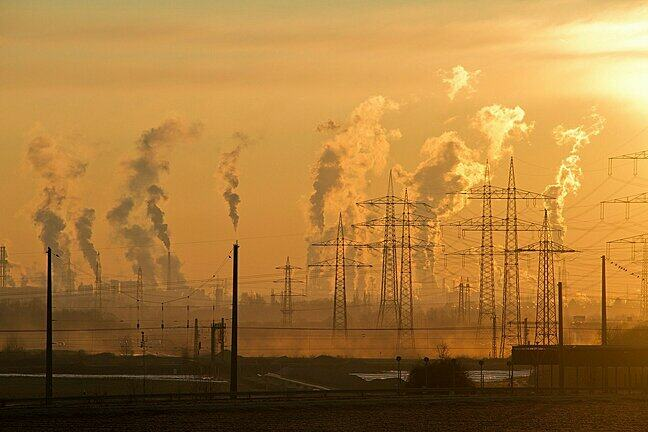 image of pollution from factories and power stations behind pylons