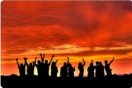 La imagen muestra un grupo de 12 personas reunido viendo la puesta del sol. Muchos de ellos están levantando sus brazos hacia el cielo. No podemos identificar sus caras de manera acertada, ya que la imagen muestra solo sus siluetas.