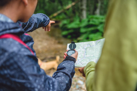 A person using a compass to navigate with a paper map in the forest