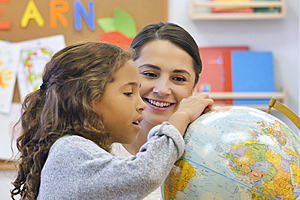 a teacher and a student looking at a globe