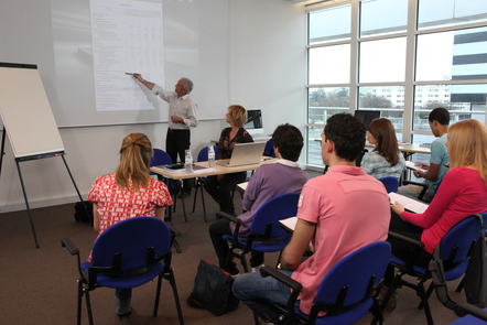 A group of learners in class with two facilitators