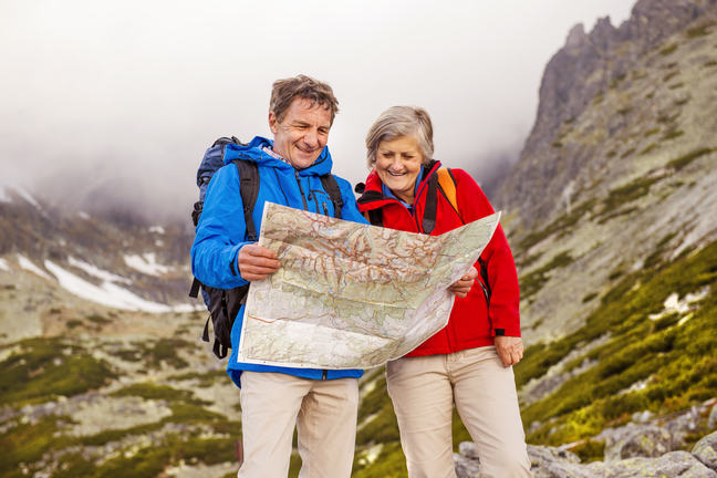 A man and a woman standing in a mountain pass looking at a map.