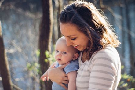 Woman smiling holding baby