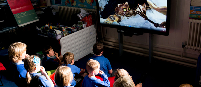 A group of primary school children gather to watch a film in their classroom.