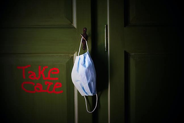 Take Care' written in red on a green door with a face mask hanging from the door handle.