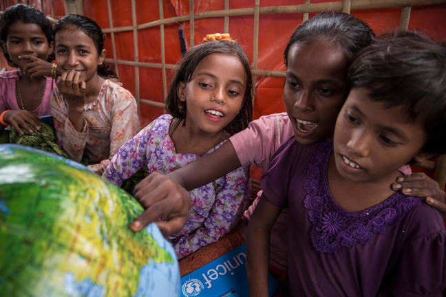 Students look at an inflatable globe, part of the educational supplies contained in a School-in-a-Box, at a new Transitional Learning Centre in the Uchiprang refugee camp, near Cox's Bazar, Bangladesh