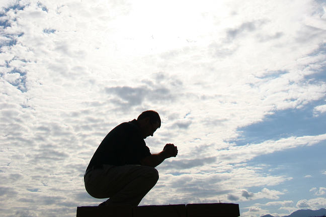 A figure in contemplation with the sky as background