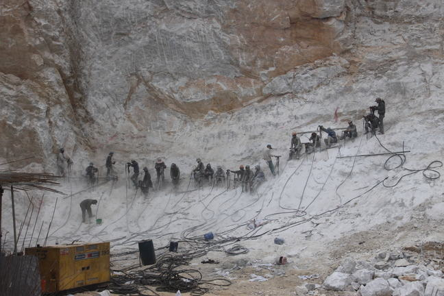 Workers on a construction site, heavily exposed to mineral dust.