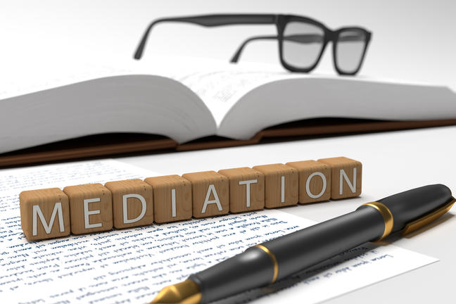 Dices containing the word Mediation, a book, glasses and a fountain pen.