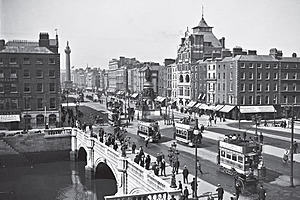 Busy Sackville St. now O'Connell Street bridge in Dublin circa July 1900. People walking up and down the pedestrian paths on the bridge while trams carry passengers in the direction of O'Connell Street.