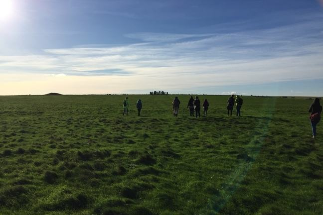 A photograph of students with Stone Henge in the background