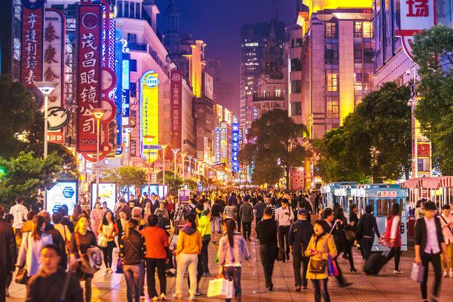 Crowds walk below neon signs at night on Nanjing Road in Shanghai