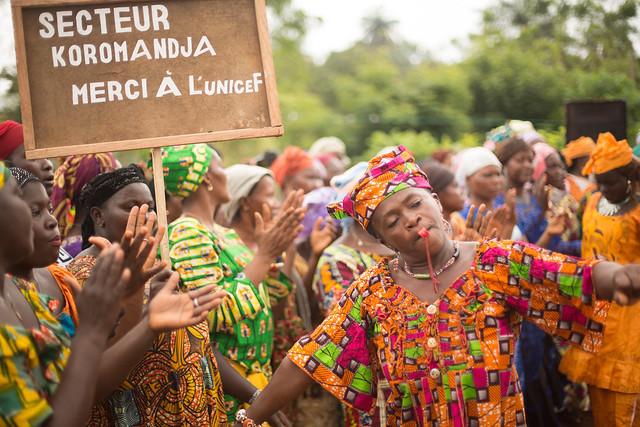 Women in colourful dress are seen dancing in celebration.