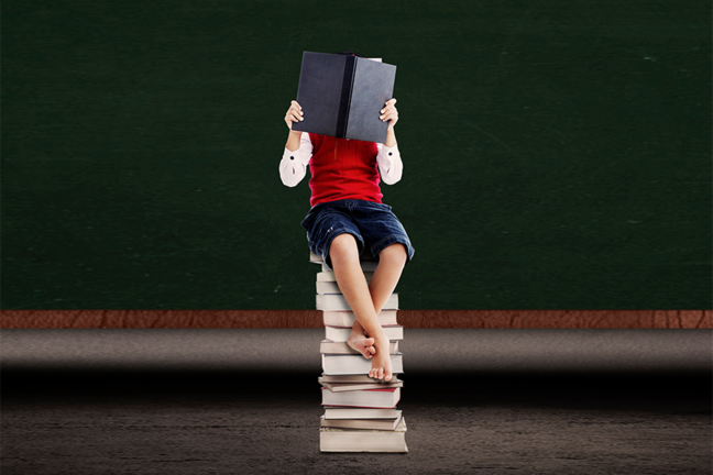 Boy sitting in a stack of books