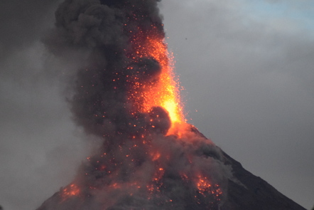 An explosive eruption occurring at the Mayon volcano with lava and black smoke being ejected out of the cone of the volcano.