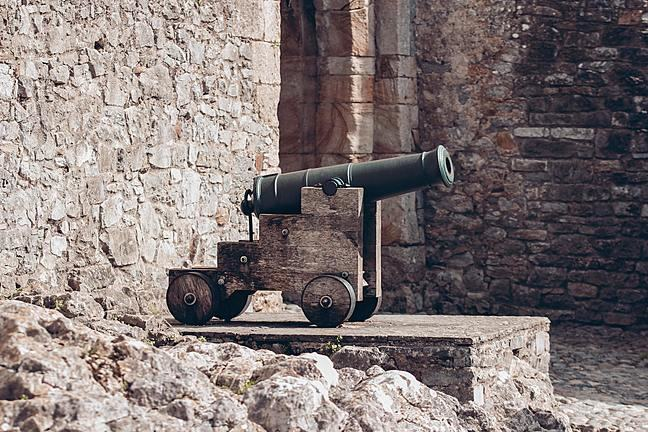 A cannon is seen in profile in front of an old stone wall.