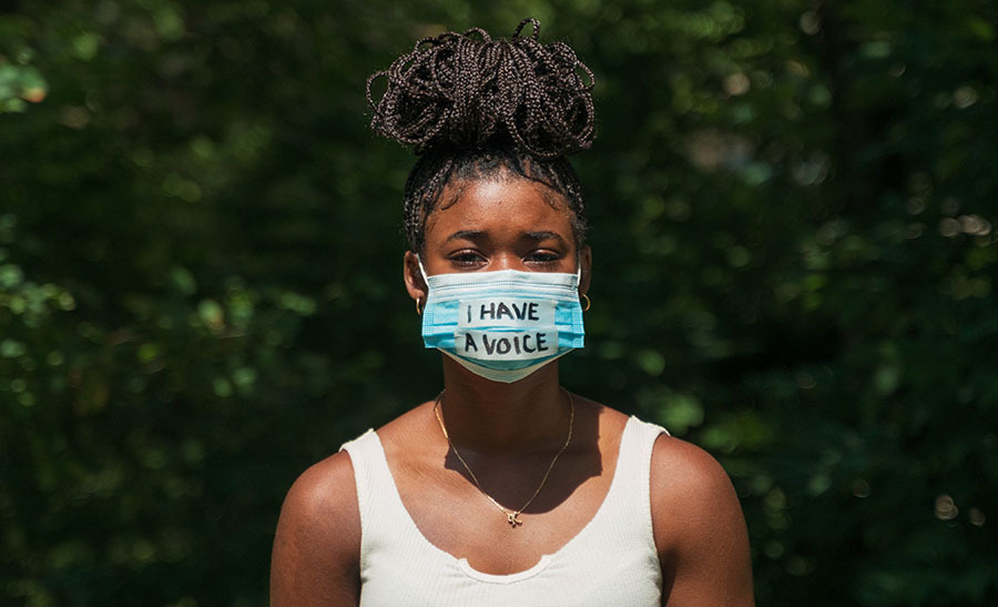 Young. black woman wearing mask with words 'I have a voice'
