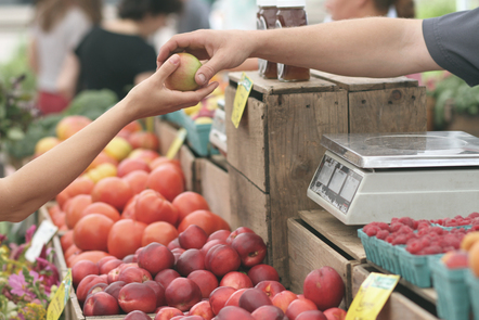 Apple being handed from one to another at a market